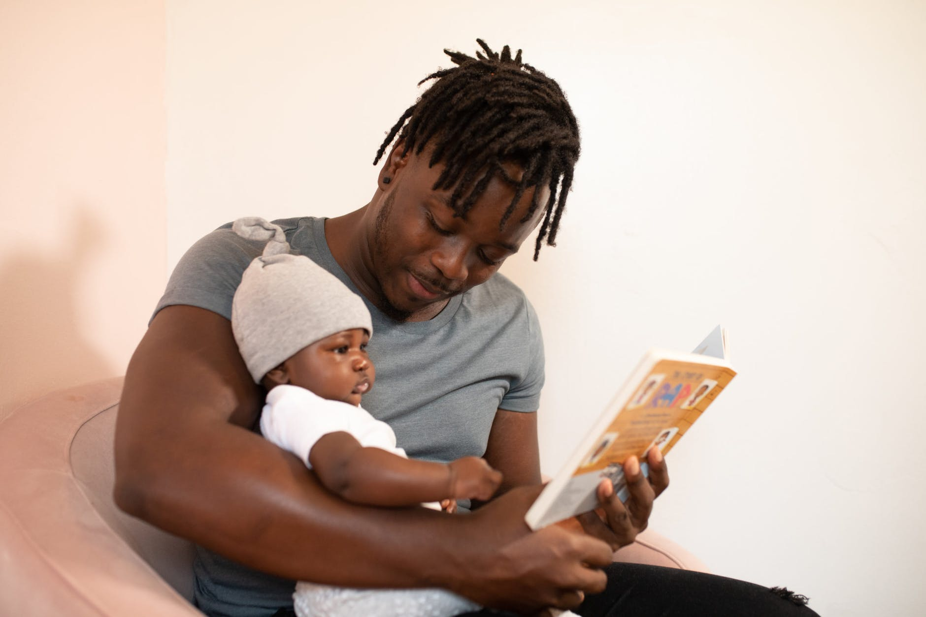 Father reading to his son in French. Both parents are only using French in the home because they know their daughter will learn English growing up in the U.S.